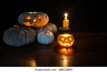 Pile of Halloween pumpkin and candle light on the wooden table in Halloween dark night / Selective focus