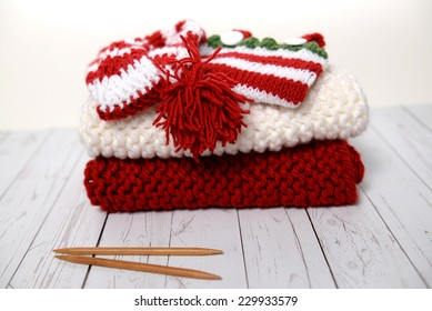 Pile of hand knit Christmas clothes
