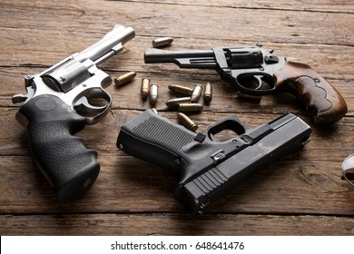 Pile of handguns on wooden table