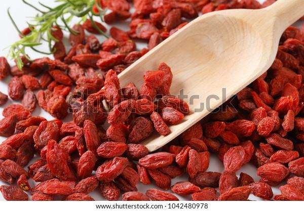 pile of healthy goji berries and woooden scoop - detail