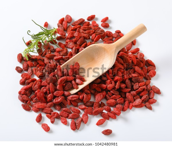 pile of healthy goji berries and woooden scoop on white background