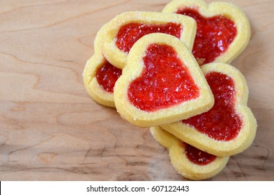 A pile of heart shaped shortbread cookies filled with red jelly