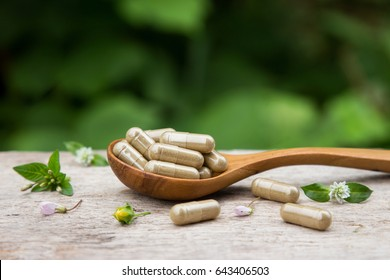 Pile of herbal capsules on wooden spoon with herbs and green natural background