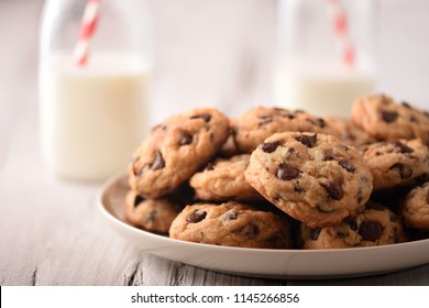 Pile of Homemade Chocolate Chip Cookies on a plate, on a wood white table, with milk bottles on the background