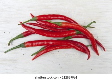 Pile of hot red chilli's on a wooden chopping board.
