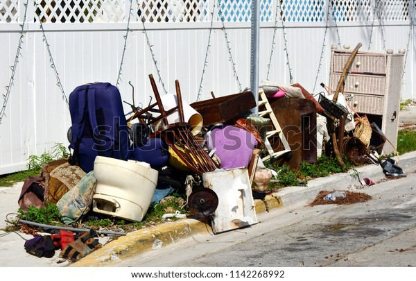 A pile of household furnishings, damaged by Hurricane Irma, placed curbside, awaiting trash removal.