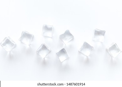Pile of ice cubes on white bar desk background top view mockup