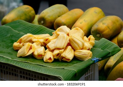 pile of jackfruits on banana leaves in local market