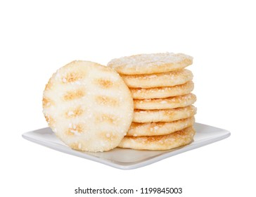 Pile of Japanese rice crackers on a small white square porcelain plate isolated on white background. Rice crackers are usually low in sugar and fat.