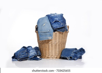 Pile of jeans and rolled Jeans in the basket-white background