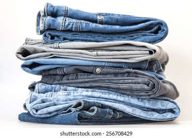 Pile of jeans of various colors on a counter in shop