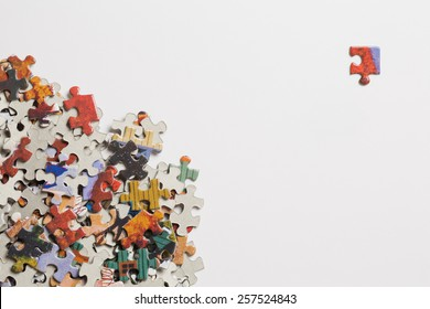 Pile of jigsaw puzzle pieces with a single corner piece separated on a white background