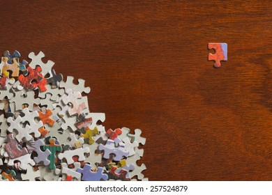 Pile of jigsaw puzzle pieces with a single corner piece separated on a dark wooden table top.