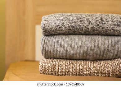 A pile of knitted sweaters on the wood bed. Warm comfortable clothes.
