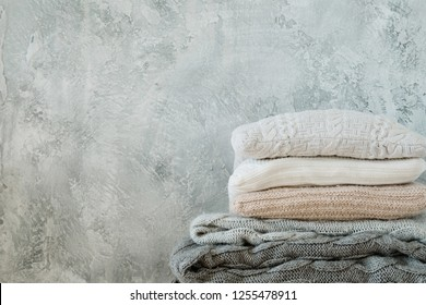 pile of knitted throw blankets and plaids on shabby gray background. warm cosy home decor