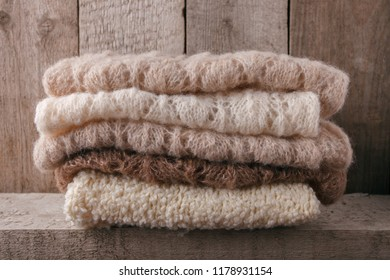 Pile of knitted winter clothes on wooden background, sweaters, knitwear, space for text, winter fall autumn concept