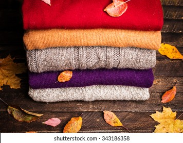 Pile of knitted winter clothes on wooden background covered with autumn leaves, knitwear, space for text. Stack of knitted sweaters and cardigans.
