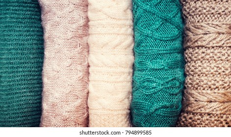 Pile of knitted wool sweaters on white background with copy space. Knitwear, clothes