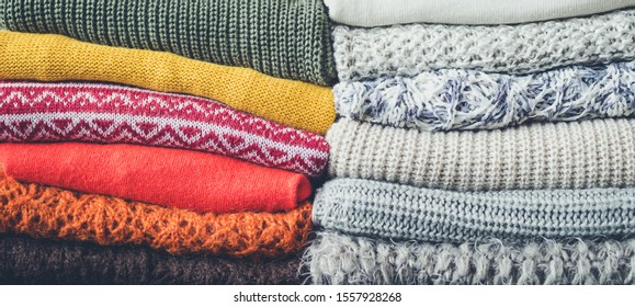 Pile of knitted woolen sweaters autumn colors. Clothes with different knitting patterns folded in stack. Warm cozy winter fall knitwear concept.