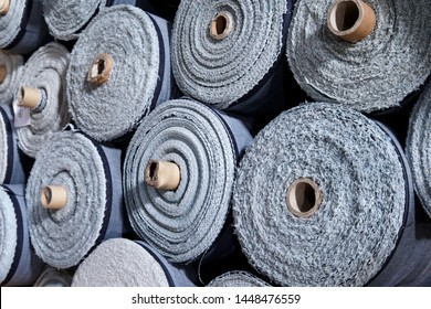 Pile of large rolls of denim fabric