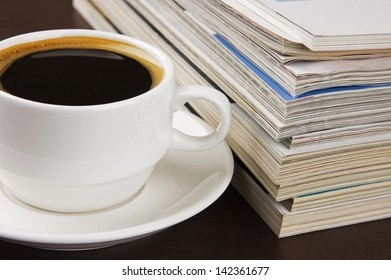Pile of magazines and cup of coffee on table