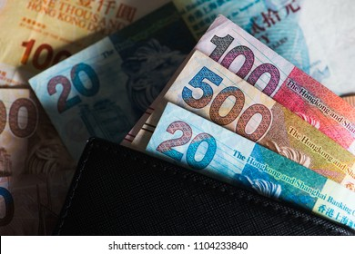 Pile of many Hong Kong Dollar banknotes with wallet as money background.