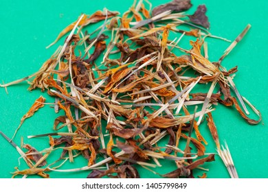 Pile of Marigold Dry Seeds (Mexican marigold, Aztec marigold, African marigold) on green background. Tagetes erecta. Daisy family.