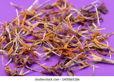 Pile of Marigold Dry Seeds (Mexican marigold, Aztec marigold, African marigold) on purple background. Tagetes erecta. Daisy family.