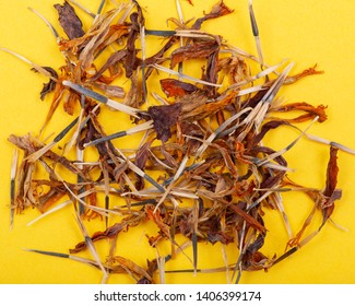 Pile of Marigold Dry Seeds (Mexican marigold, Aztec marigold, African marigold) on yellow background. Tagetes erecta. Daisy family.