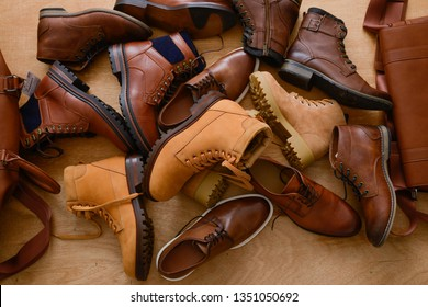 Pile of Men's brown leather shoes and wooden background