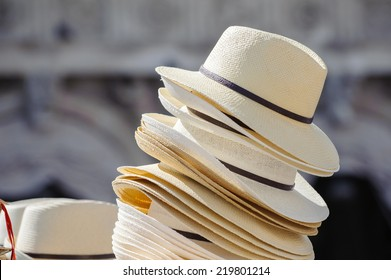 A pile of men's hats on a stall in sunshine; necessary protection against the sun and risk of skin cancer, especially melanoma.