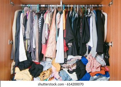 Pile of messy clothes in closet. A lot of cluttered woman outfit wardrobe.