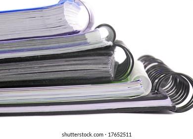 a pile of metal ring binder notebooks