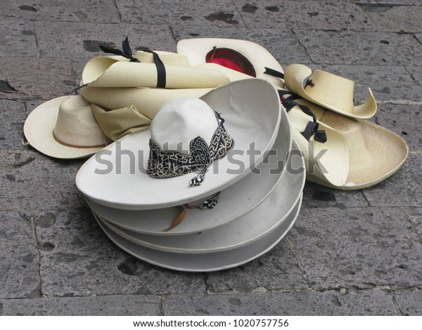 eef18f5f1512d0 A pile of Mexican sombreros, cowboy hats, and other wide-brimmed hats for