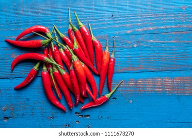 Pile of  mini red ripe chili hot peppers on blue wooden background , selective focus,closeup.