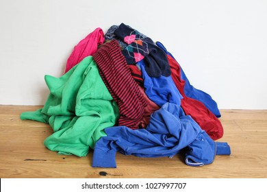 Pile of mixed dirty colorful clothes ready for washing on the wooden floor near the white wall, concept of house cleaning