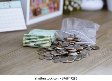 Pile of money coins and bank closeup on work desk background. Concept of financial saving