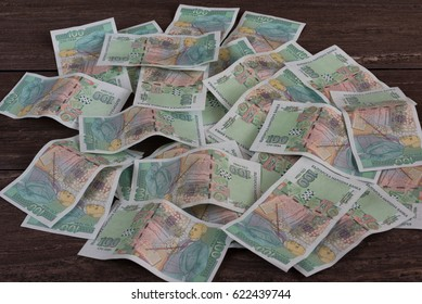 Pile of money on grey wooden board.