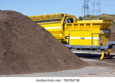 Pile of mulch at a green recycle plant ready to be fed into an industrial grinder to make compost