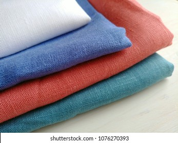 Pile of natural colorful linen fabrics, handmade kitchen, tea, hand towels on white wooden background. Different colours. Food photo props. Natural linen cotton fabric.