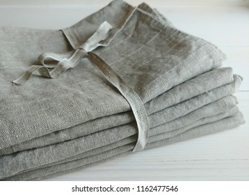 Pile of natural linen towels, napkins on white wooden background.