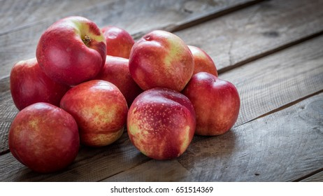 Pile of nectarines on the wooden background.
