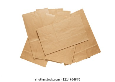 Pile of new kraft paper bags laying flat  isolated on white background . Brown paper bags with clipping path .