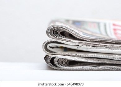 Pile of newspaper on a white table.