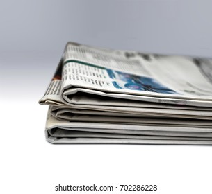 Pile of newspapers;  differential focus, graduated neutral background; good copy space