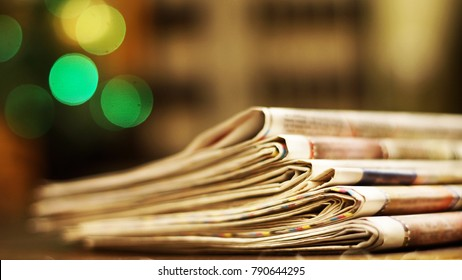 Pile of newspapers. Folded and stacked pages with news, headlines, articles and photos on the wooden table. Daily papers under Christmas tree in the morning. Selective focus, blurred background