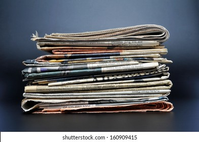 Pile of newspapers on black background