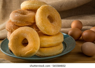 pile off fresh donuts in a plate with some eggs on background