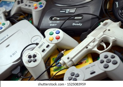 Pile of old 8-bit video game consoles and many gaming accessories like a joysticks and cartridges