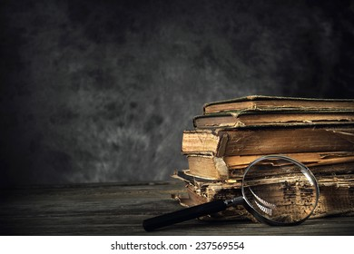 Pile of old antique and yellowed books with a magnifying glass in a dark, grungy library